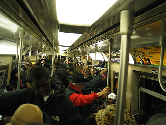 Interior of a crowded subway car on 7 train Queens bound late evening. Image taken by Daniel Schwen on Dec 6th, 2004. {{GFDL}} via Wikimedia Commons