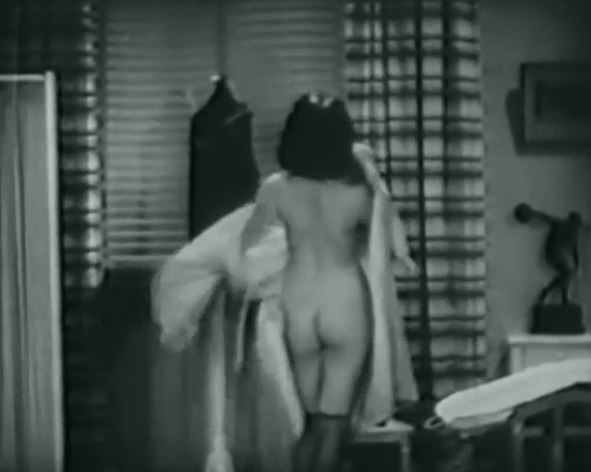 Black and white picture of a woman disrobing.