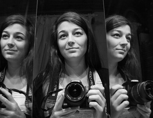 Woman with camera reflected twice in mirror.