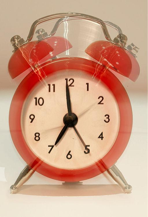 Photo of an old-fashioned orange alarm clock ringing