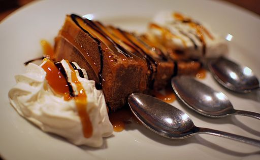slice of cheesecake with caramel sauce and 3 spoons