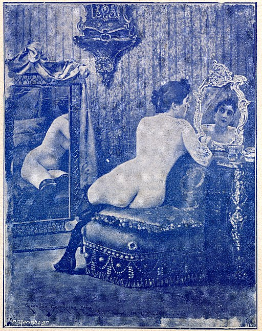 vintage photo of a nude woman looking at herself in a mirror